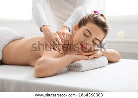 Joyful young lady with closed eyes getting relaxing back massage at spa, side view. Pretty woman attending modern spa salon, laying on massage table, enjoying healing body treatment