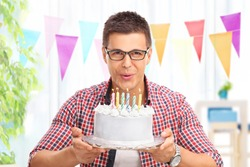 Joyful young man blowing candles on a birthday cake and looking at the camera at home