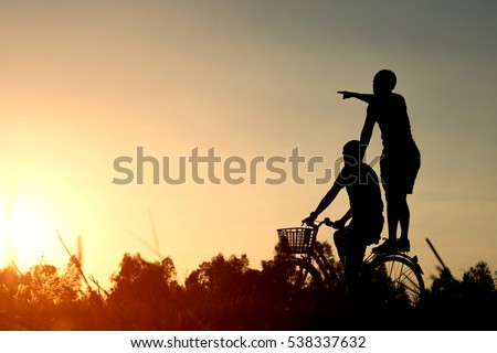 Joyful young man riding a bicycle together. Best friends having fun on a bike at the meadow.