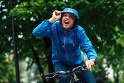 Joyful young man standing with his bike before bicycling on a rainy day next to the house. Happy curly male courier in blue raincoat delivers parcel cycling with a bicycle.