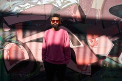 Joyful young multiracial bearded guy standing with hands in his pockets in front of the wall with graffiti at the sunny street. Urban lifestyle and activity concept