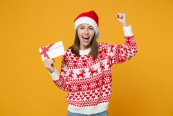 Joyful young Santa woman in red sweater Christmas hat hold gift certificate doing winner gesture isolated on yellow colour background studio portrait. Happy New Year celebration merry holiday concept