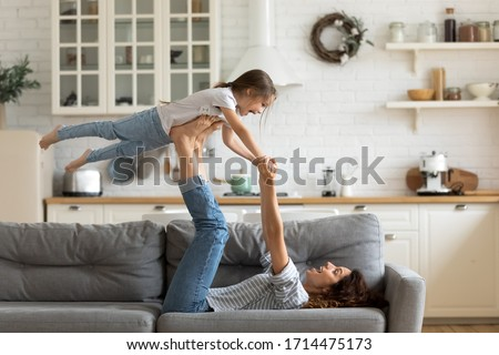 Joyful young strong woman lifting on legs arms laughing little child daughter, having fun together on cozy sofa in modern studio living room. Overjoyed small kid girl practicing acroyoga with mom.
