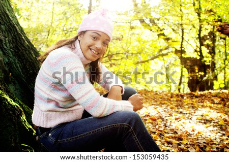 Joyful young teenager girl sitting on a textured tree trunk and smiling while visiting an autumn forest park during a sunny golden day during the fall season, outdoors.