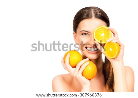 Joyful young woman holding juicy oranges before her eyes. Healthy eating concept. Diet. Isolated over white.  Zdjęcia stock ©