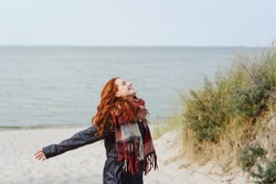 Joyful young woman in a warm winter scarf celebrating the cold weather as she enjoys a day outdoors on the beach in winter flinging back her arms with a happy smile