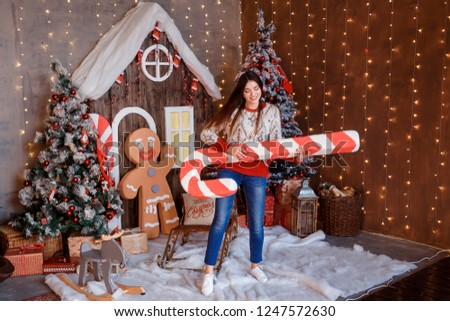 Joyful young woman is playing on enormous candy cane like it is a guitar. Having fun in Christmas festive interior. Garlands of lights, gingerbread man and Gingerbread house decorations.
