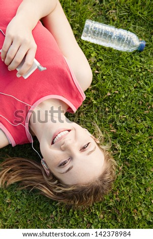 Joyful young woman laying down on a park green grass, taking a break from exercising while listening to music with her mp4 player and earphones.