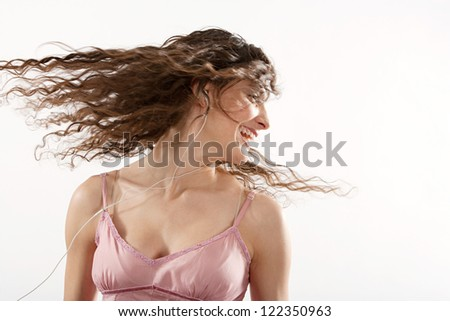 Joyful young woman listening to music with her headphones and shaking her hair in the air to the rhythm and smiling, isolated on a white background.