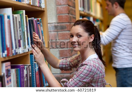 Joyful young woman looking for a book in a bookstore