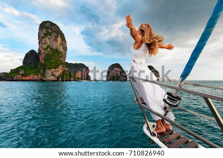 Joyful young woman portrait. Happy girl stand on board of sailing boat have fun discovering islands in tropical sea on summer coastal cruise. Travel adventure, yachting with kids on family vacation.