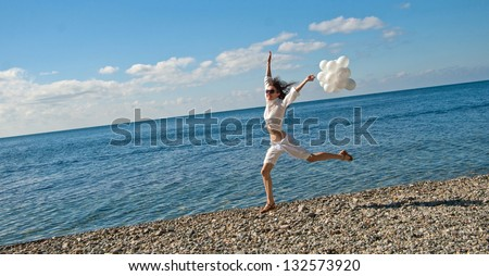 Joyful young woman running along the seashore holding white balloons