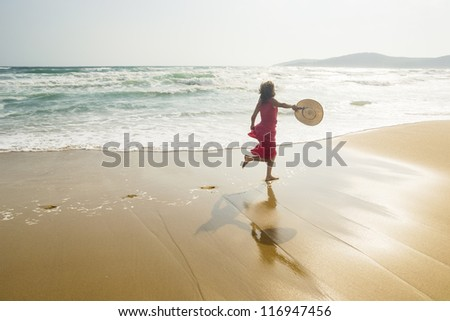 Joyful young woman running along the sunny beach