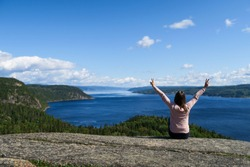 Joyful young woman sitting on a rock admiring the beautiful Saguenay fjord