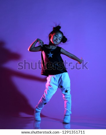 Joyfull asian kid girl in shirt and pants with stars on purple background dances with closed eyes like a disco star #1291351711