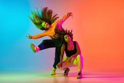 Joyfull dance. Credative lifestyle. Two beautiful hip-hop dancers in motion on gradient blue orange backlground in neon. Sport expression. Concept of dance, youth, hobby, dynamic, movement, action, ad