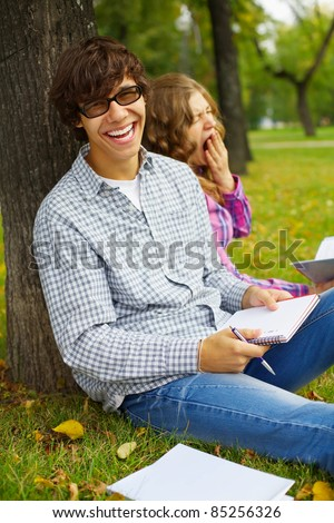 Joyfull smiling teen boy and yawning girl sitting under tree with books and notebooks in autumn park outdoor