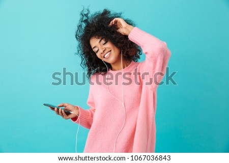 Joyous american woman in casual clothing dancing and listening to music with pleasure via white earphones isolated over blue background