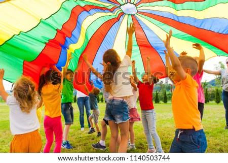 Joyous classmates jumping under colorful parachute