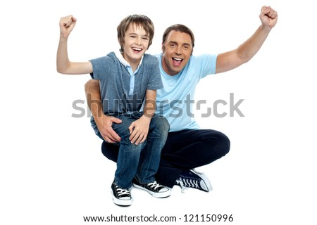 Joyous father and son cheering loud. Supporting their favorite teams.