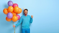 Joyous optimistic man celebrates successful job position, being on corporate party, clenches fist in triumph, holds bunch of colorful balloons, wears blue outfit, party hat, stands indoor, copy space