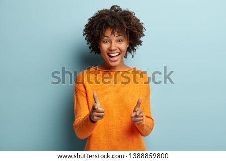 Joyous pretty African American lady makes finger gun gesture at camera, expresses choice, smiles broadly, dressed in orange jumper, isolated over blue background, says you are chosen. Bang, bang