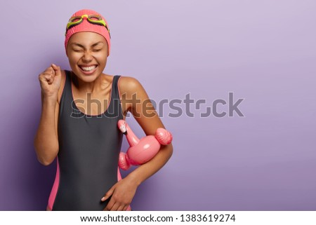 Joyous slim woman wears black swimsuit, swimming hat and goggles, clenches fists, celebrates learning how to swim, holds pink summer flamingo float, isolated on purple wall. Watersport concept #1383619274