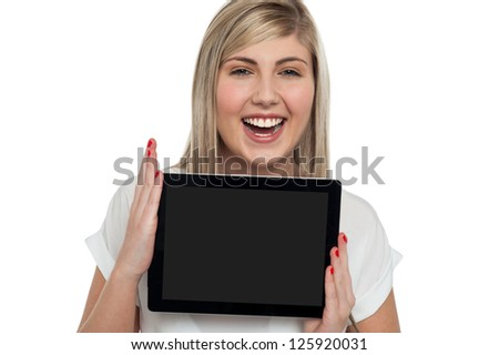 Joyous teen caucasian girl displaying a brand new tablet pc, touch screen device.