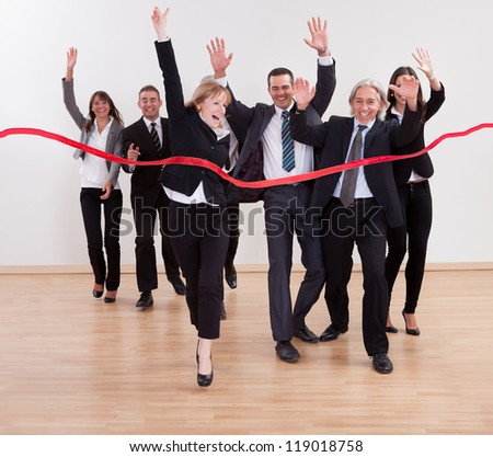 Jubilant business people celebrating raising their arms in the air and shouting as they cut the red ribbon to begin a new business venture