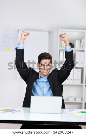 Jubilant businessman sitting in front of his open laptop with his fists raised in the air and a beaming smile of success - stock photo