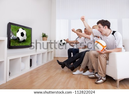 Jubilant family watching television as they cheer on their home side in a sporting competition