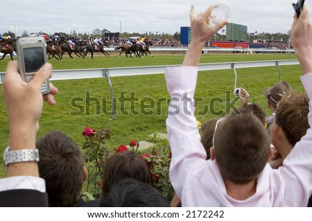 Jubilant spectators encourage their horses across the line