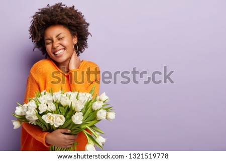 Jubilant upbeat black woman has curly hair, broad shining smile, keeps hand on neck, eyes shut, wears orange sweater, holds white flowers with pleasant scent, models over purple studio wall. Spring