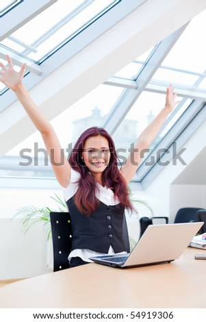 jubilating female clerk with laptop sitting in office