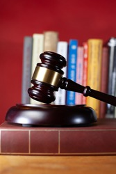 judge gavel and books on red background