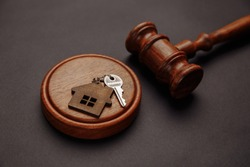 Judge gavel and key chain in shape of two splitted part of house on wooden background. Concept of real estate auction or dividing house when divorce, division of property, real estate, law system