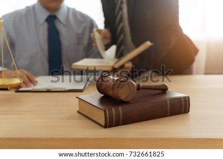 Judge gavel, law books with lawyer team meeting at law firm in background. Concepts of law,legal, ligislation.