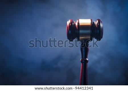 judge gavel on blue background with smoke and dramatic lighting