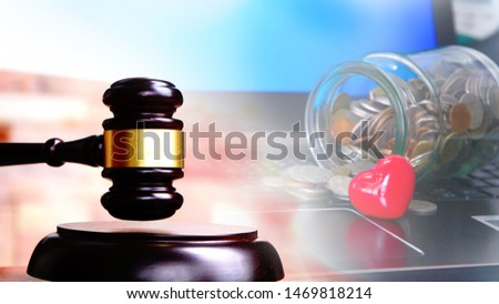 Judge gavel on keyboard laptop with jar money coins and red heart.Prosecution for medical damages or Health Litigation  concept.