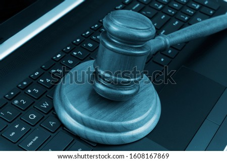 Judge gavel on laptop computer keyboard, cyber law and crimes concept