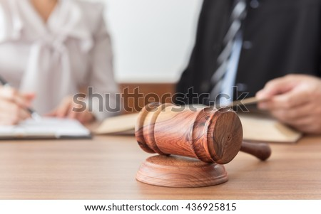 Judge gavel with lawyers having team meeting in law firm background. Concepts of legal services.