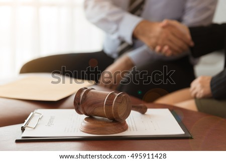 Judge gavel with legal documents and attorney hold hands client and give legal advice. #495911428