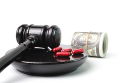 Judge hammer, pill capsules and money banknotes over white background