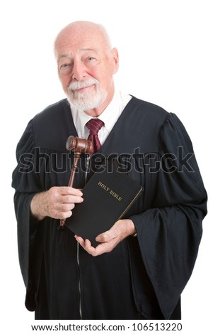 Judge holding his gavel and a bible.  Metaphor for balancing church and state.  Isolated on white.