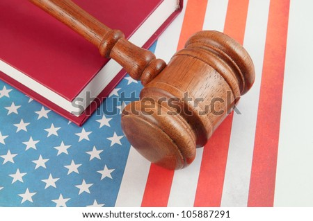 Judge's gavel and legal book on united states flag
