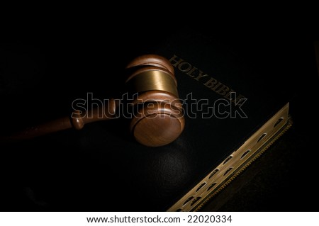 Judge's gavel laying on top of a black holy Bible
