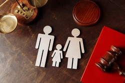 Judge's gavel on a red book and family figures. Family law