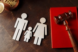 Judge's gavel on book and family figures