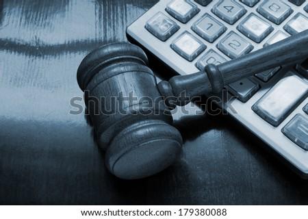 Judge's gavel on calculator, arbitration concept - stock photo