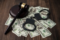 Judge's gavel with handcuffs on the background of dollar bills, a judge's hammer, American dollar bills, handcuffs on a wooden background. arrest, deposit.